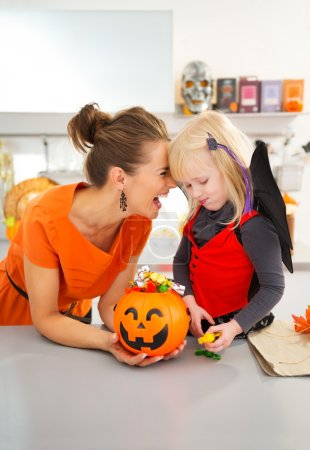 Portrait of happy mother with daughter in halloween bat costume
