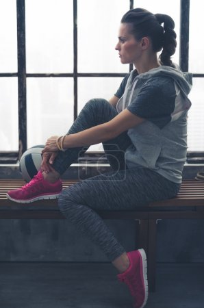 Photo for A woman is sitting relaxing while sitting on a wooden bench in a loft gym. She is lost in thought, looking into the distance, zoning out. On the bench lies a ball. Her pink running shoes add colour. - Royalty Free Image