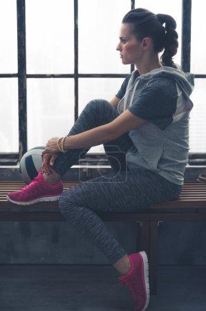 Pensive woman in workout gear looking in profile in loft gym