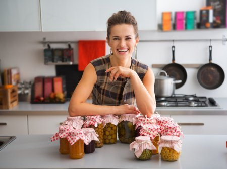 Happy, proud woman in kitchen with jars of home-preserved fruits