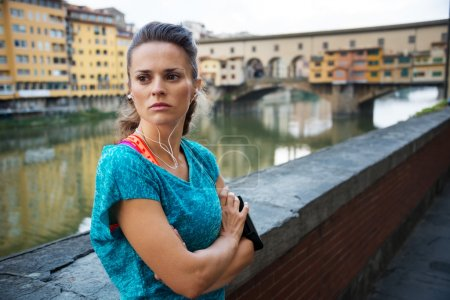 Young woman in sportswear is staying next to Ponte Vecchio