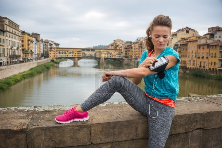 Sporty young woman sitting and listening mp3 player