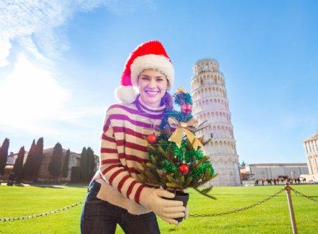 Photo pour Jeune, démangeaisons d'énergie et recherche d'excitation. Je vais à Noël en Italie. C'est une évidence. Heureuse femme dans le chapeau de Père Noël tenant arbre de Noël en face de penché Tour de Pise . - image libre de droit