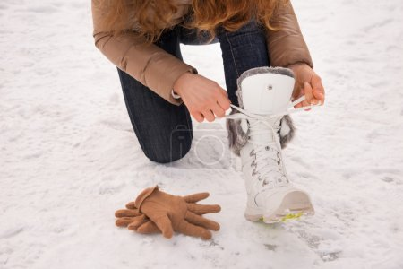 Photo for Energy-filling and exciting winter weekends in the mountains. Closeup on woman tying shoelaces without gloves outdoors - Royalty Free Image