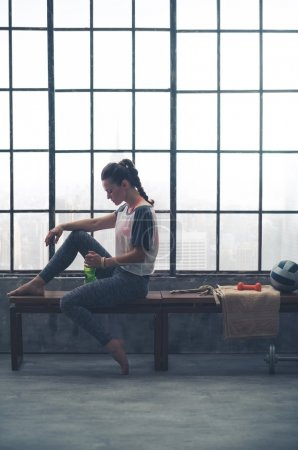 Photo for Relaxing and peaceful after a good yoga workout, a woman sits quietly on a wooden bench by the window in a loft gym. - Royalty Free Image