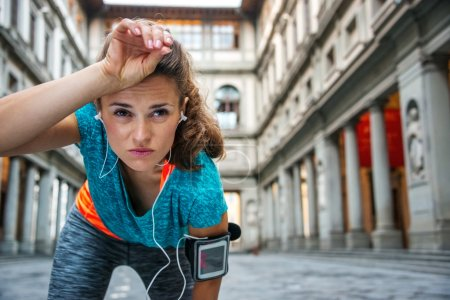 Young woman in sportswear is catching breath