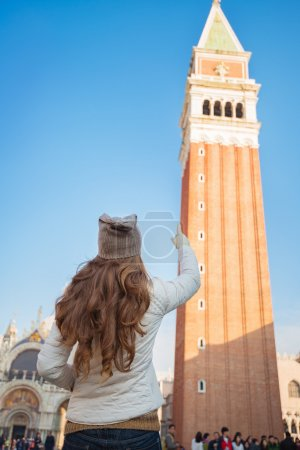 Seen from behind woman pointing on tower of St Mark's Basilica