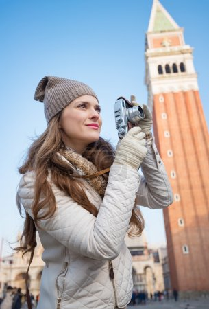 Photo for Take classical tourist enjoyment in Venice, Italy - wander over San Marco square, chase pigeons and take photos. Young woman taking photos with retro photo camera in front of Campanile di San Marco - Royalty Free Image