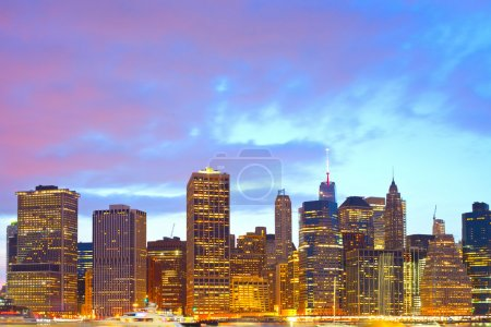 Photo pour New York City skyline, financial district colorful illuminated buildings in downtown Manhattan at sunset - image libre de droit
