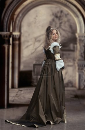 Photo pour Belle femme en robe médiévale, regardant en arrière, fond intérieur - image libre de droit
