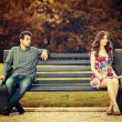 Young couple sitting apart on the bench in the par...