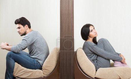 Photo pour Conflit entre l'homme et la femme assis de chaque côté d'un mur - image libre de droit