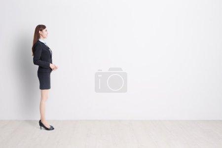 Photo pour Femme d'affaires stand profil avec fond de mur blanc, idéal pour votre conception ou texte, asiatique - image libre de droit