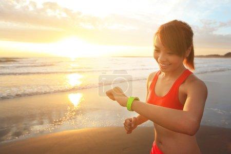 Photo pour Coup d'oeil et santé sport jeune femme courir portent périphérique intelligent montre avec écran tactile sur la plage au lever du soleil, asiatique - image libre de droit