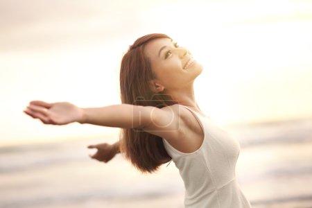 Photo pour Sourire Femme de liberté et de bonheur sur la plage. Elle profite de la nature paisible de l'océan pendant ses vacances à l'extérieur. la beauté asiatique - image libre de droit