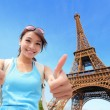 Happy woman in Paris giving  thumbs up...