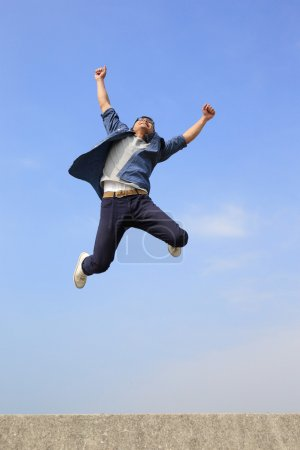 Photo for Happy College student jumping with blue sky on  background - Royalty Free Image