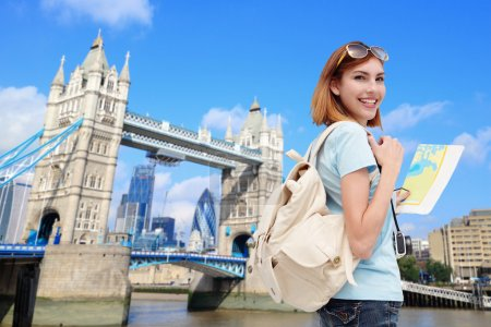 Photo pour Happy woman holding map  with tower bridge on background - image libre de droit