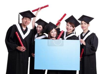 Photo pour Groupe d'étudiants diplômés heureux montrant le panneau d'affichage vierge, isolé sur fond blanc - image libre de droit