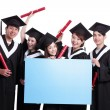 Group of happy graduate students showing blank bil...