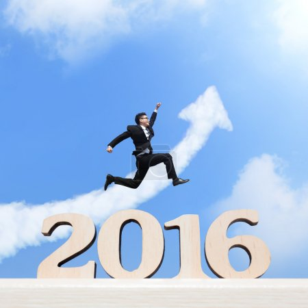 Photo for Happy new year for 2016 - successful  business man jumping  in the air cheering and celebrating over  wood number - Royalty Free Image