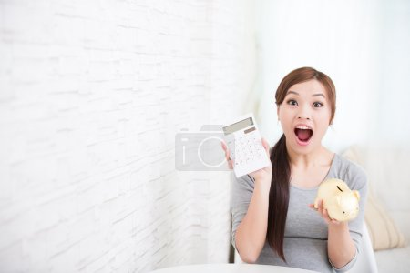 Photo pour Jeune femme sourire tenir calculatrice et tirelire à la maison, concept d'entreprise, de la beauté asiatique - image libre de droit