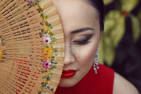 Beautiful asian female portrait with red dress and lips sitting on the green floral background holding wooden fan with flower pattern near her face