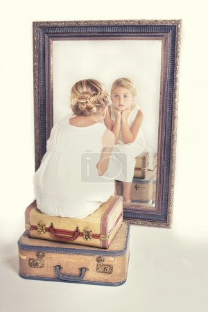 Child or young girl staring at herself in a mirror