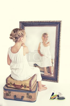 Child fixing her hair while looking in the mirror.