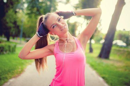 Photo pour Portrait d'une fille sportive s'entraînant et s'étirant dans le parc tout en écoutant de la musique, concept de fitness - image libre de droit