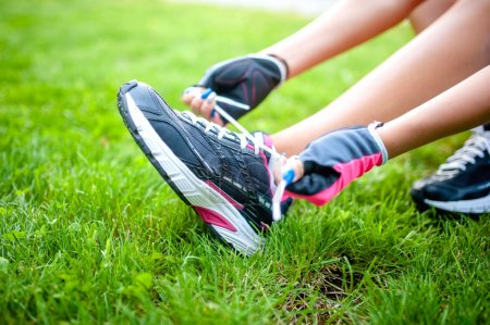 Close-up of active jogging female runner, preparing shoes for training and working out at urban fitness park