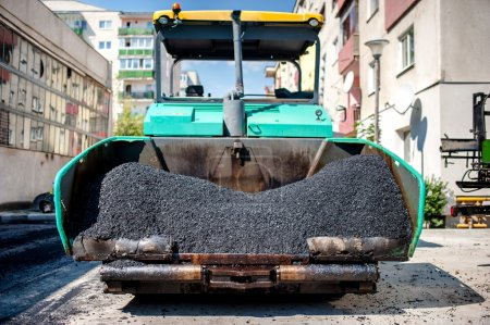 Industrial paver laying fresh asphalt and bitumen pavement on top of gravel layer during road construction