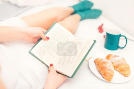 Close-up of sexy woman reading a book in bed with croissant as breakfast and fluffy warm socks