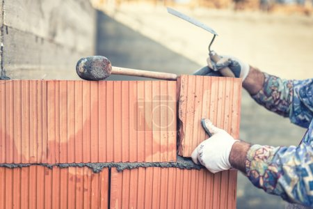 Construction bricklayer worker building walls with  bricks and mortar