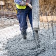 Building construction worker pouring cement or con...