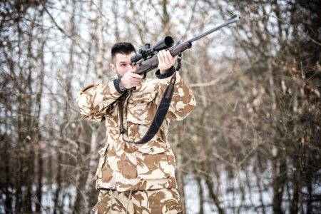 Photo pour Sniper avec arme prête pour le combat ou la chasse dans la forêt un jour d'hiver - image libre de droit