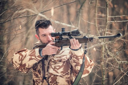 Man holding a sniper and shooting on an open season, looking through scope