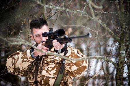 Photo pour Chasse, armée, concept militaire - sniper tenant un fusil et visant une cible dans la forêt pendant l'opération - image libre de droit