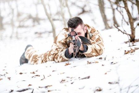 Photo pour Jeune sniper visant à travers la portée et tirant avec un fusil pendant l'opération concept de guerre ou concept de chasse - image libre de droit