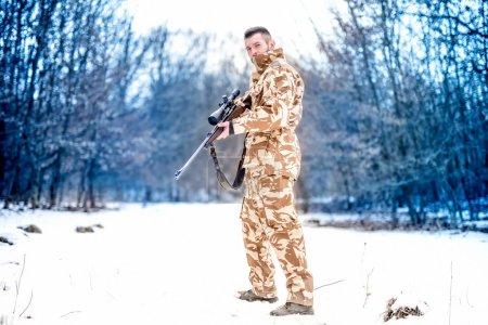 Photo pour Sniper de l'armée lors d'une opération militaire à l'aide d'un fusil professionnel par une journée froide d'hiver - image libre de droit