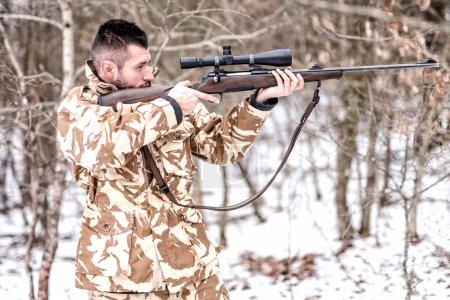 Photo pour Chasseur avec sniper visant et tirant dans la forêt pendant la saison de chasse d'hiver - image libre de droit