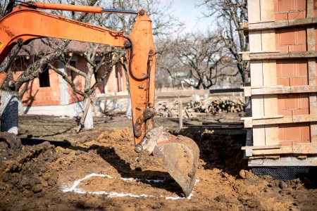 excavator scoop on construction site, digging earth and loading dumper trucks.