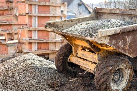 Dumper truck unloading construction gravel, sand and curshed stones