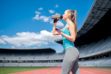 Portrait of healthy fitness girl drinking protein shake during workout on stadium