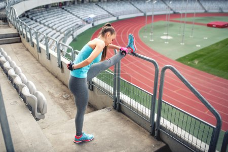 Female athlete training and stretching for warming up on the stairs. Fitness girl training and running