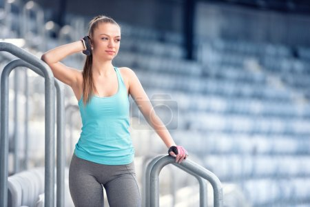 Young woman resting at training, preparing for marathon, jogging and running concept. Fitness trainer resting between sets on stairs