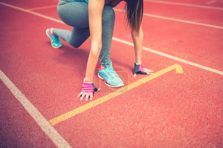 Athlete on starting blocks at stadium track preparing for a sprint. Fitness, healthy lifestyle concept