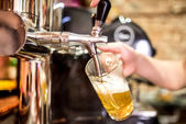 Mano del barista presso birra toccare versando una birra lager alla spina che serve in un ristorante o un pub