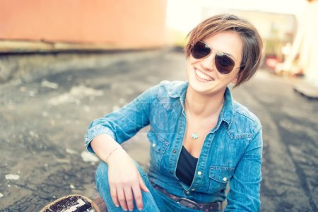 Trendy brunette girl, smiling and laughing against orange background, isolated. Hipster instagram girl smiling at camera, urban lifestyle