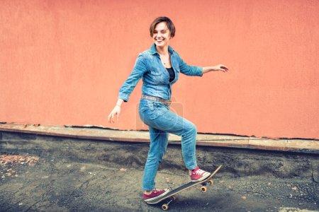 Photo pour Portrait artistique d'une fille mignonne brune sur une planche à roulettes, riant et s'amusant. Concept sain de la vie moderne, fille hipster avec skateboard sur le toit - image libre de droit